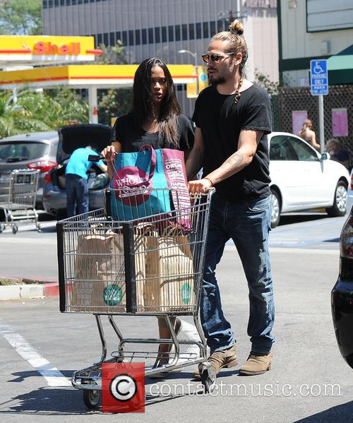 Zoe Saldana and Marco Perego hold hands while...