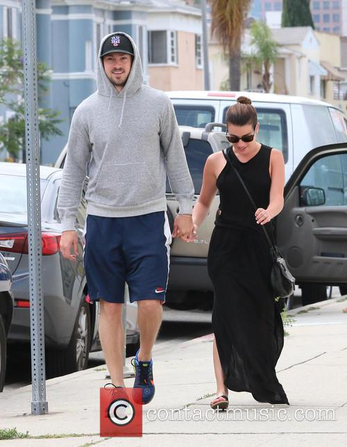 Lea Michele and Matthew Paetz hold hands while...