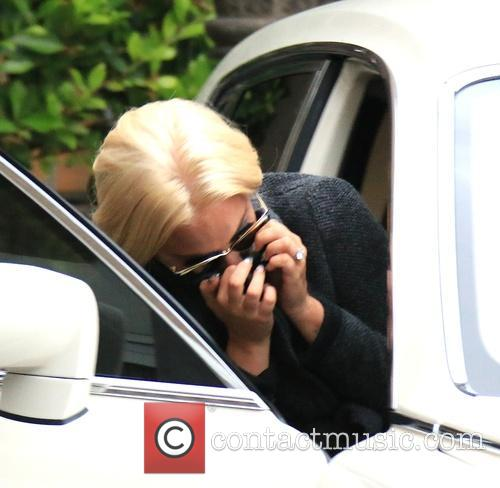 Lady Gaga hides her face as she leaves...