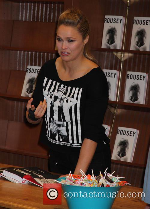 UFC Champion Rhonda Rousey sings copies of her...