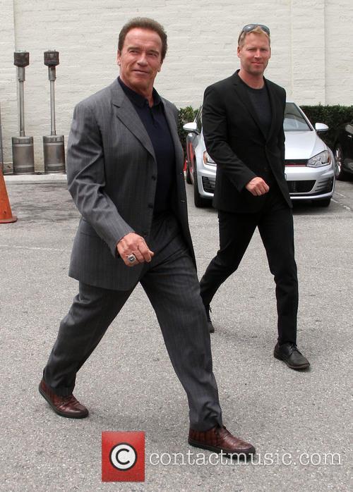 Arnold Schwarzenegger carrying his Apple laptop
