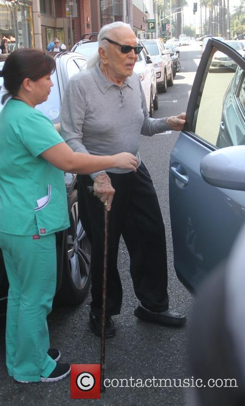 Kirk Douglas is helped to his car as...