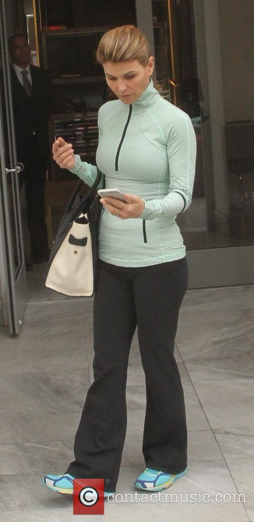 Lori Loughlin checks her cellphone as she goes...