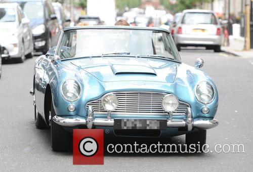 Chris Evans driving a blue convertible Aston Martin...