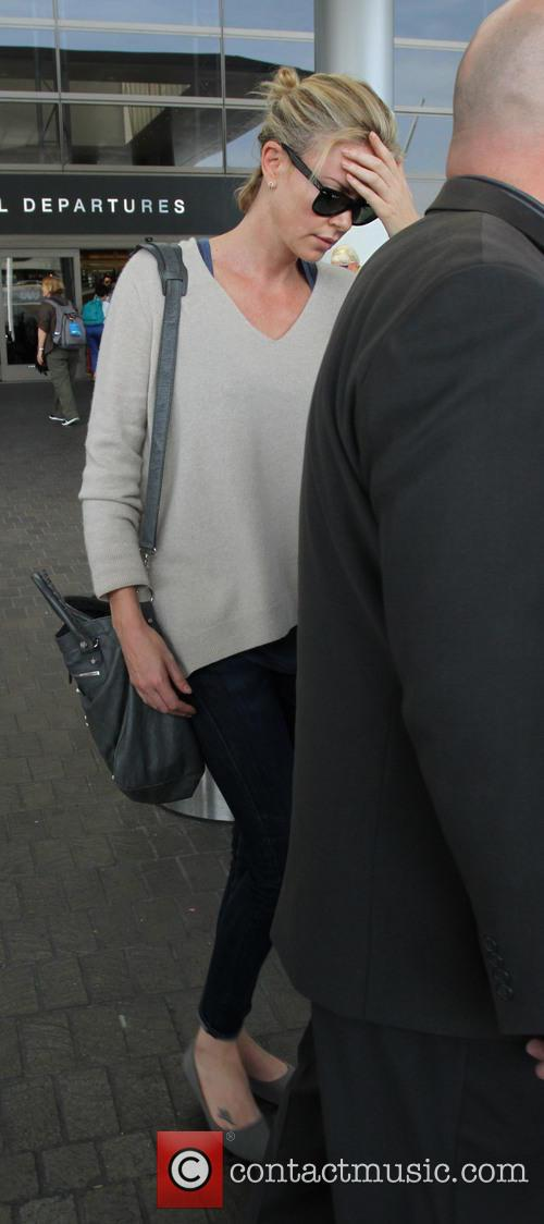 Charlize Theron arrives at Los Angeles International Airport...