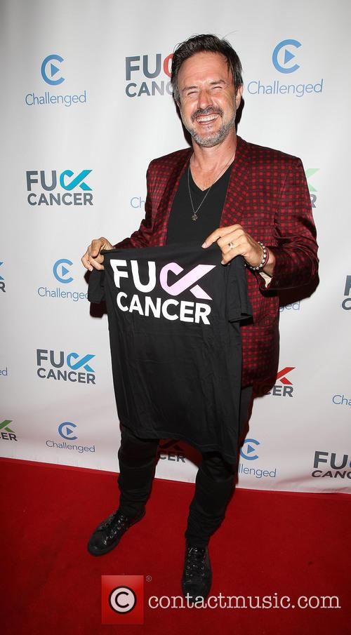 David Arquette holding a t-shirt supporting 'Fuck Cancer'