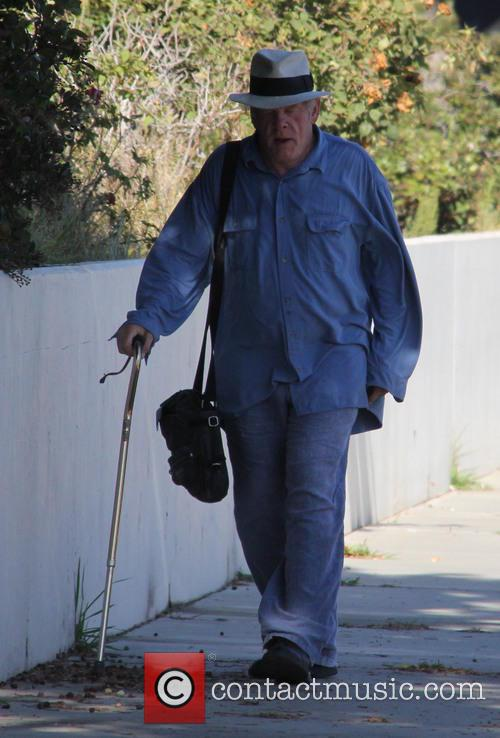 Nick Nolte walking with the aid of a...