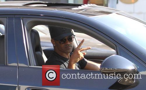 Shemar Moore makes a hand gesture while driving