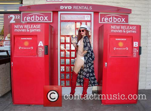 Phoebe Price poses in front of a Red...