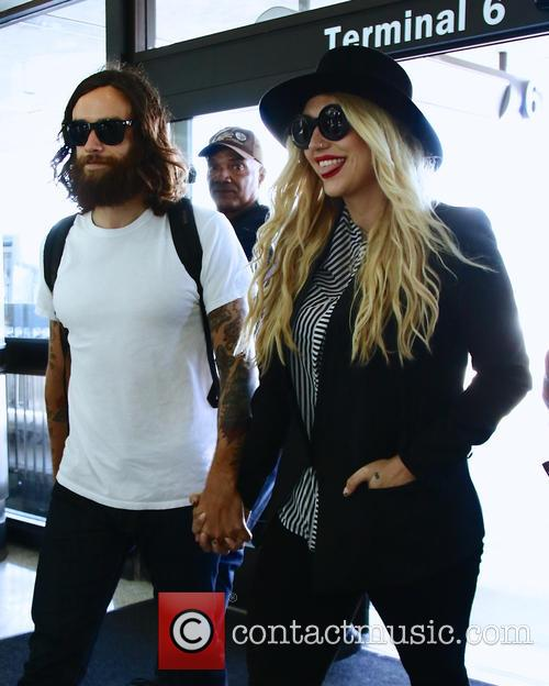 Kesha holds hands with her boyfriend Brad Ashenfelter...