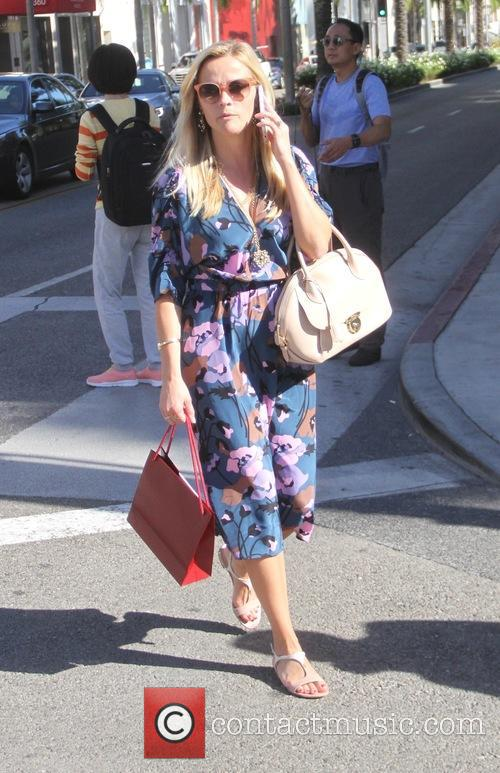 Reese Witherspoon wearing a blue floral dress goes...
