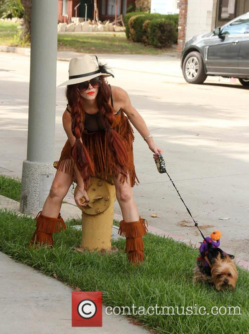 Phoebe Price wears a Pocahontas-like outfit while walking...