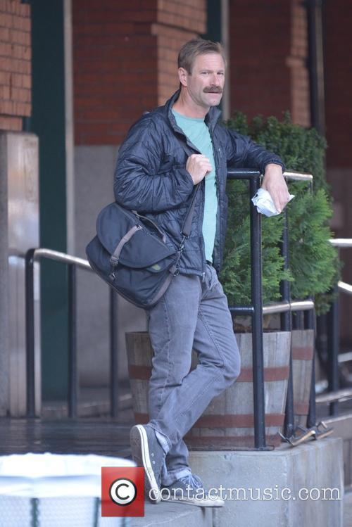 Aaron Eckhart sports a bushy mustache while out...