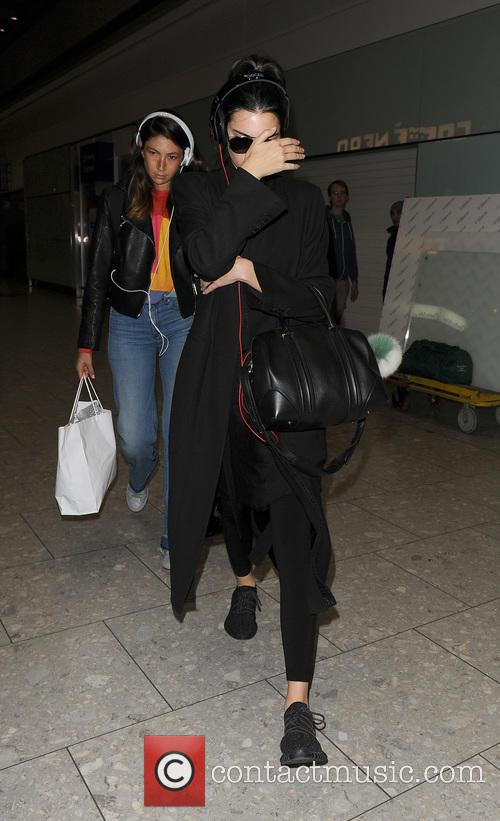 Kendall Jenner appears camera shy as she arrives...