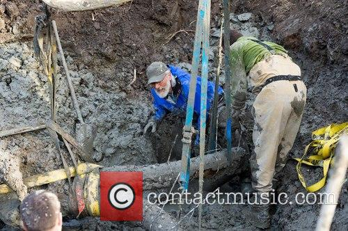 Daniel Fisher and Joe El-adli Guide The Mammoth's Right Tusk As The Skull Is Carefully Lifted From The Excavation Pit With A Backhoe. 1