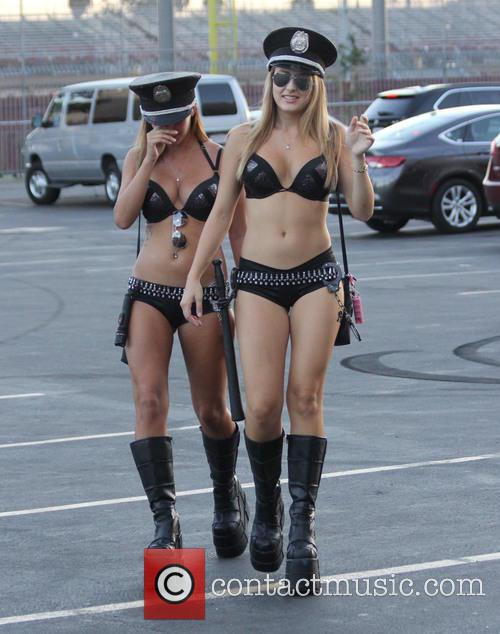 Two scantily clad women dress as security officers...