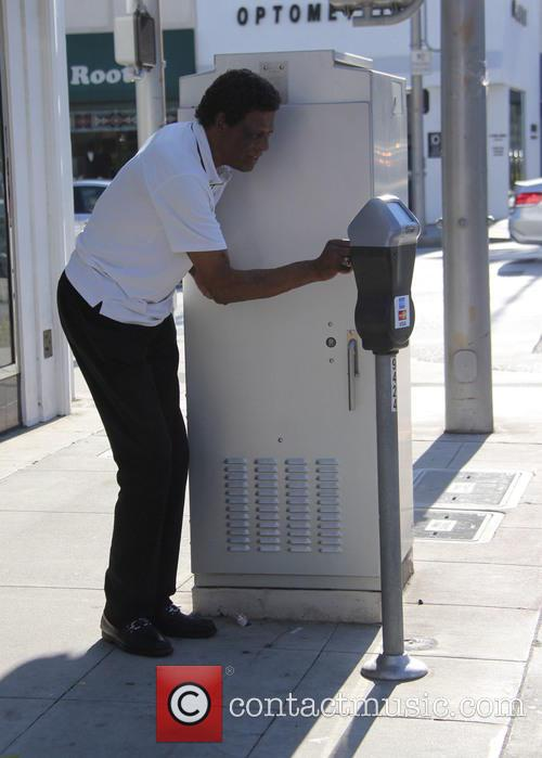 Elgin Baylor feeds a parking meter with coins