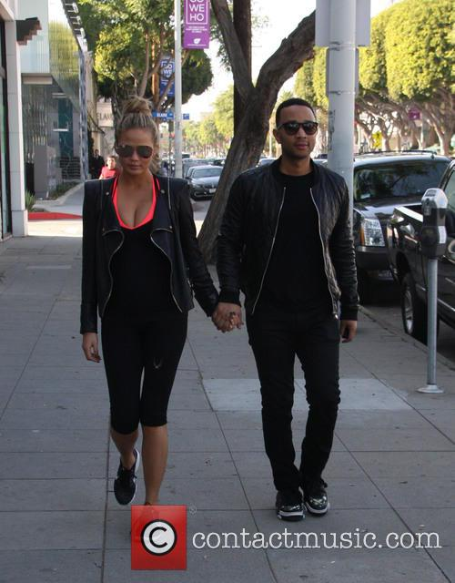 Chrissy Teigen and John Legend hold hands while...