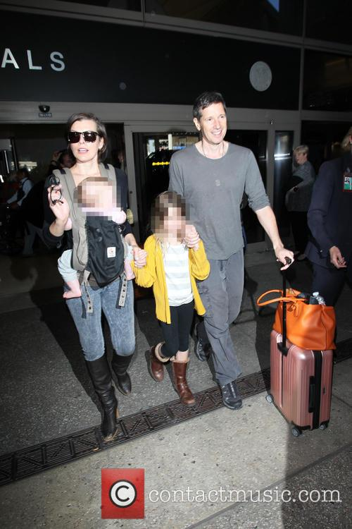 Milla Jovovich and family arrive on a flight...