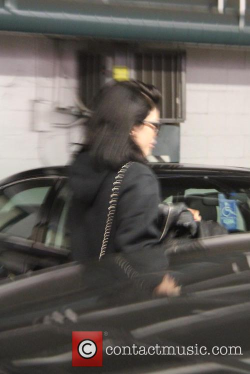 Kylie Jenner hides from paparazzi behind her jacket...