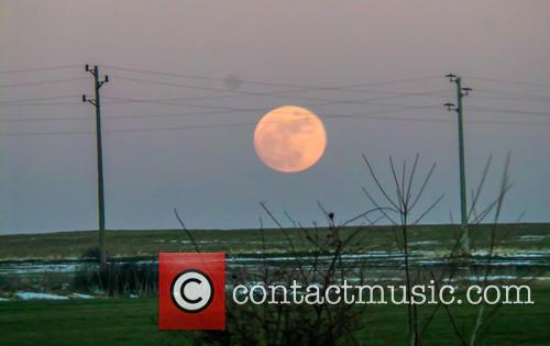 A Full Wolf Moon is seen over the...