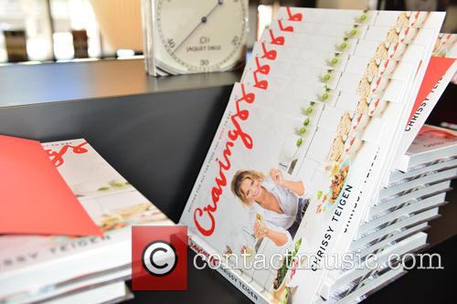 Visibly pregnant Chrissy Teigen signs copies of her...