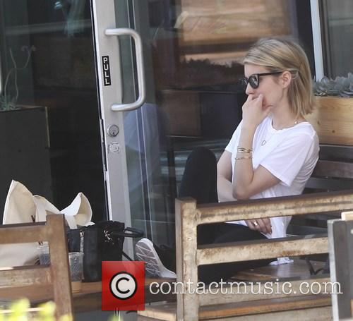 Emma Roberts picks up a cold beverage while...