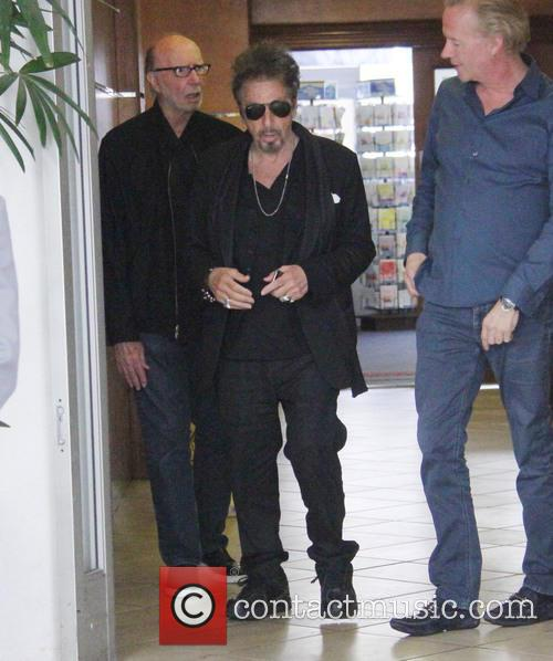 Al Pacino poses with fans as he leaves...