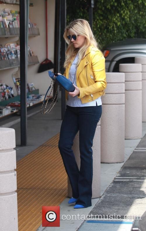 Reese Witherspoon stops by a newsstand to buy...