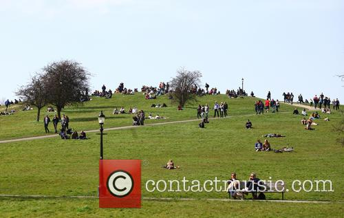 People enjoy the sunny weather on Primrose Hill