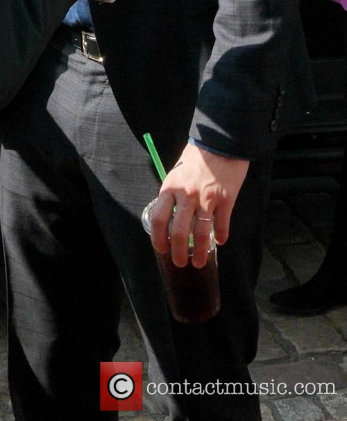 Ashton Kutcher wears his wedding ring while he...