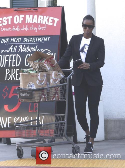 Kelly Rowland smiling for the cameras after shopping...