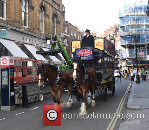 An old horse-drawn omnibus is seen making it's...