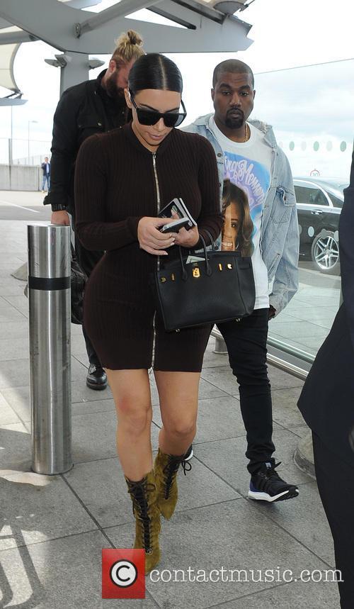 Kim Kardashian and Kanye West arrive at Heathrow...