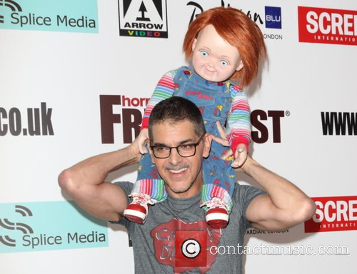Don Mancini poses with the creepy Chucky doll