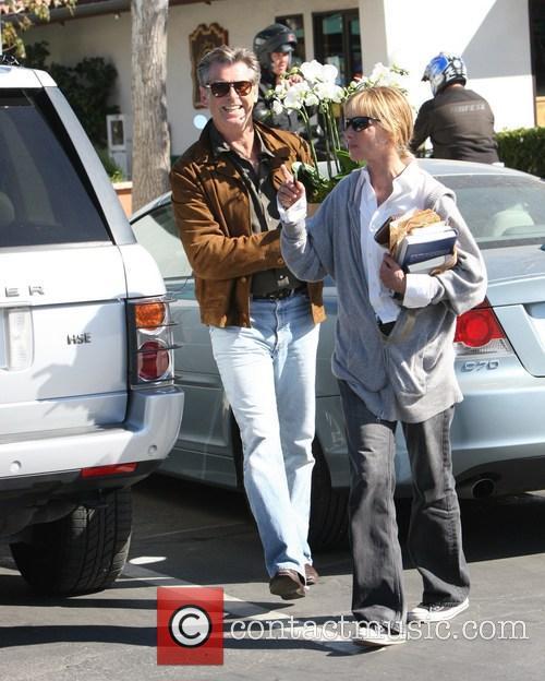 Pierce Brosnan is all smiles as he carries...