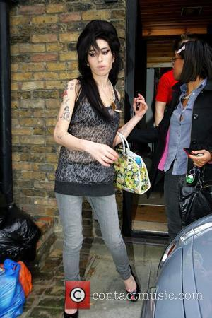Amy Winehouse leaves her home this afternoon to see husband Blake at Pentonville prison. Amy appears to have new scratches...