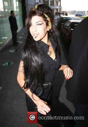 Amy Winehouse smokes a cigarette while leaving her hotel the morning after her satellite link-up to accept her five Grammy...