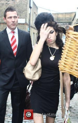 Amy Winehouse leaves her North London home carrying a mirror, as she removes the last of her belongings out of...