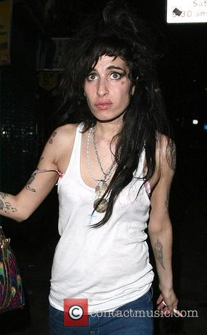 Amy Winehouse and a female do a spot of late night shopping, having left a bar in Camden at 3.30am....