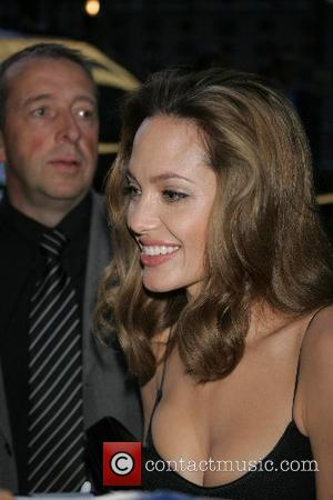 Angelina Jolie Brad Pitt and Angelina Jolie sign autographs for fans as they arrive at the New York Premiere of...