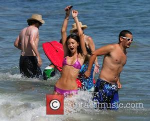 Model Caroline DeMore enjoys a day on the beach with friends sunbathing, swimming and playing with a dog. Wearing a...