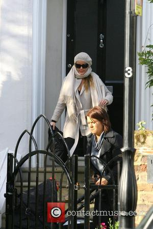 Davinia Taylor leaves her house with her nanny and son Grey. Davinia certainly wrapped up warm wearing a wooly scarf...