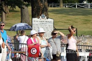 Fans have been walking up the Graceland Mansion's drive to visit Elvis Presley's grave, holding a candle each to pay...