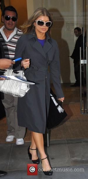 Fergie aka Stacy Ann Ferguson shops at Calvin Klein on Madison Avenue wearing her new purchases as she leaves New...