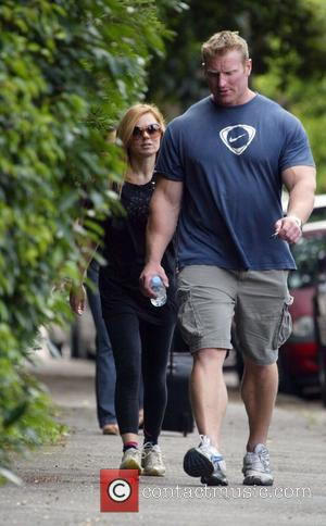 Geri Halliwell returns home after a workout with her man mountain instructor Tim Blakely. Geri is currently getting in shape...