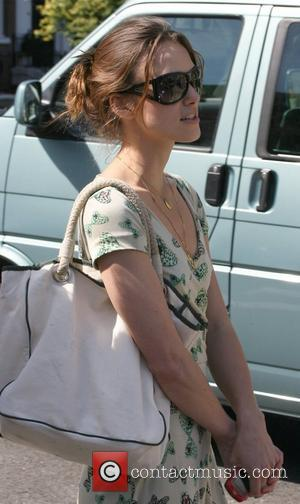 Keira Knightley tries to avoid photographers by hiding behind dark shades