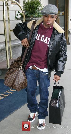 Gospel singer Kirk Franklin carrying a large shopping bag while leaving his Manhattan hotel