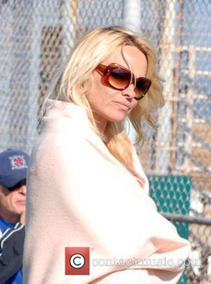 Pamela Anderson arrives at a baseball park, dressed in an oversized shawl and sunglasses, to watch her sons play in...