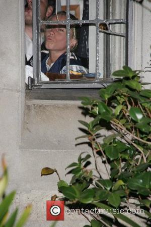 Kendra Wilkinson peering out through a window from inside the mansion, but not wanting to come out and join the...